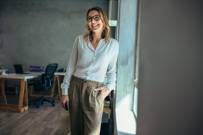 Empresaria sonriente que se coloca en oficina imagen de archivo libre de regalías