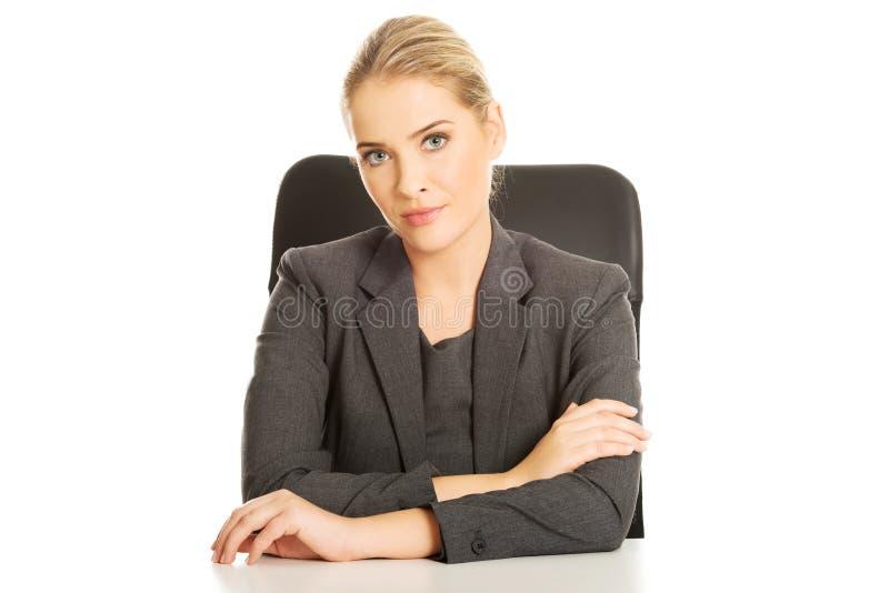 Empresaria sonriente que se sienta en el escritorio imagenes de archivo