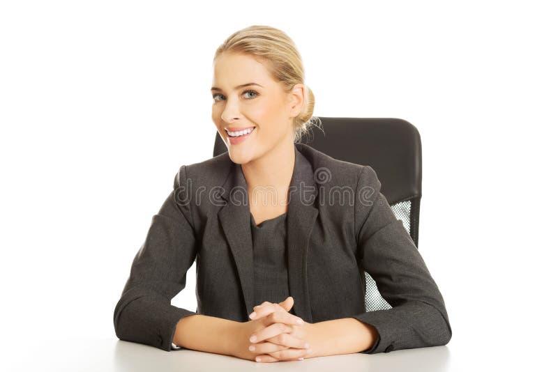 Empresaria sonriente que se sienta en el escritorio foto de archivo