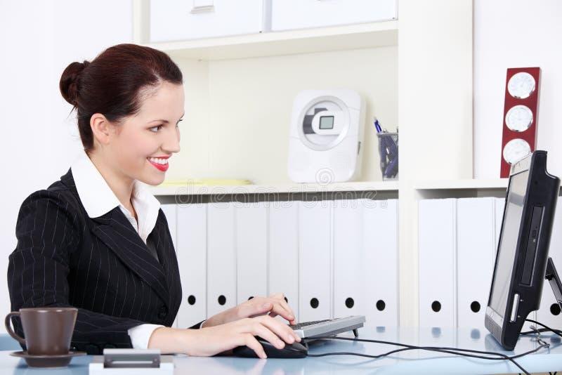 Empresaria sonriente que se sienta por el ordenador. foto de archivo libre de regalías