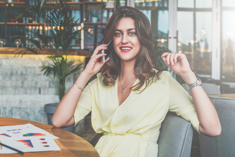 Empresaria sonriente que se sienta solamente en la tabla en café y que llama por el teléfono celular fotografía de archivo libre de regalías
