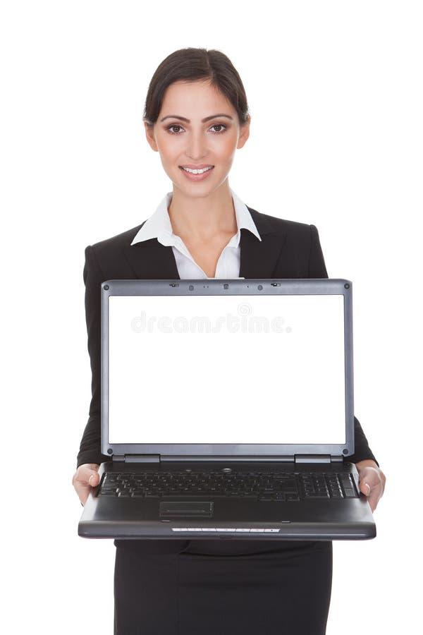 Empresaria sonriente que sostiene el ordenador portátil foto de archivo libre de regalías