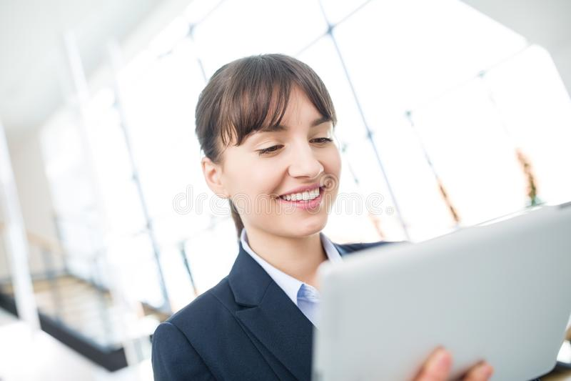 Empresaria sonriente que usa la tableta digital en oficina foto de archivo libre de regalías