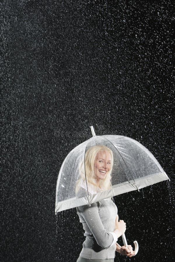 Empresaria sonriente Standing Under Umbrella durante la lluvia imágenes de archivo libres de regalías