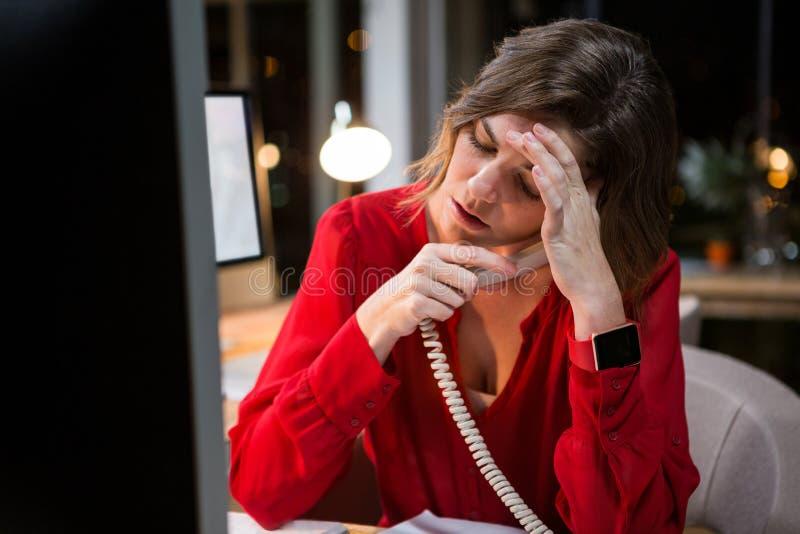 Empresaria subrayada que habla en el teléfono en su escritorio fotografía de archivo libre de regalías