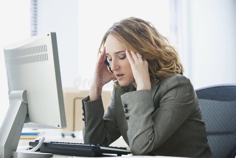 Empresaria tensionada que trabaja en oficina imagenes de archivo