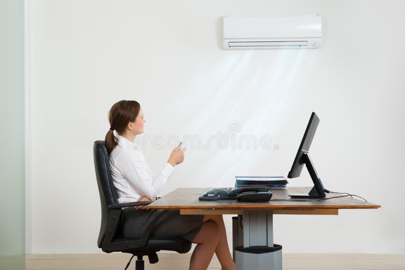 Empresaria Using Air Conditioner en oficina imagenes de archivo