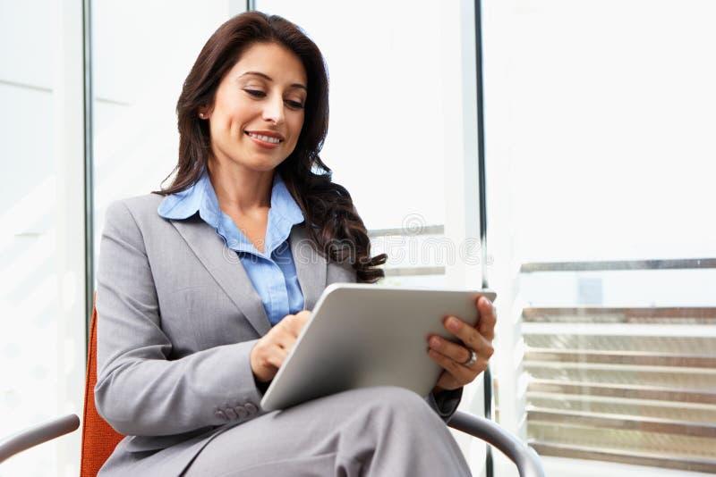 Empresaria Using Digital Tablet en oficina fotografía de archivo
