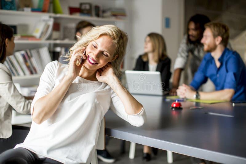 Empresaria Using Mobile Phone en oficina imagenes de archivo