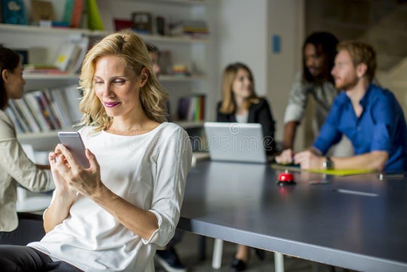 Empresaria Using Mobile Phone en oficina imagen de archivo