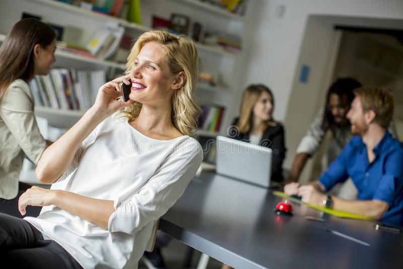 Empresaria Using Mobile Phone en oficina imágenes de archivo libres de regalías