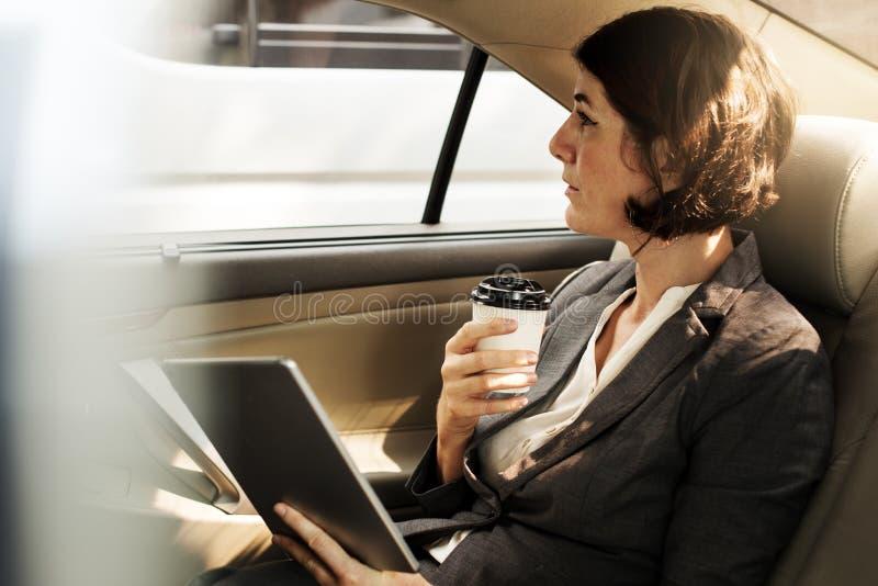 Empresaria Using Tablet Car dentro fotografía de archivo
