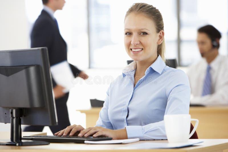 Empresaria Working At Desk en oficina ocupada fotos de archivo