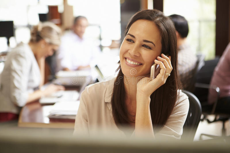 Empresaria Working At Desk que usa el teléfono móvil imágenes de archivo libres de regalías