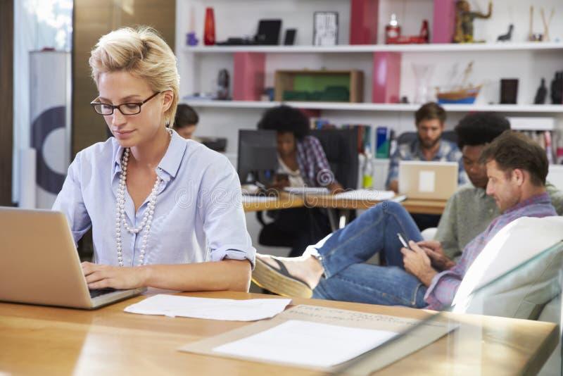 Empresaria Working On Laptop en oficina ocupada imagen de archivo