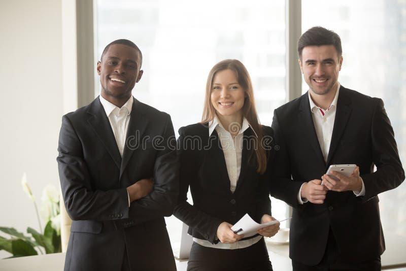 Empresaria y dos hombres de negocios que presentan para la cámara, multi-ethni fotografía de archivo libre de regalías