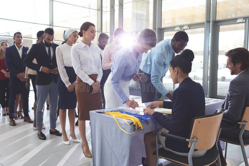 Empresaria y hombre de negocios que firman adentro en la tabla del registro de la conferencia foto de archivo