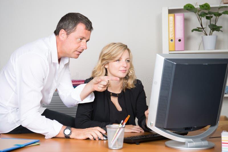 Empresaria y jefe del hombre de negocios que mira el ordenador foto de archivo libre de regalías