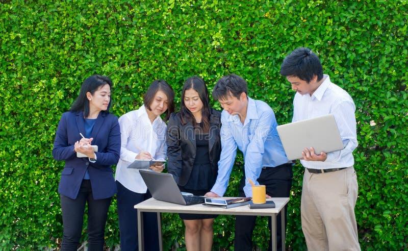 Empresaria y reunión del hombre de negocios fuera de la oficina usando lapto fotografía de archivo libre de regalías