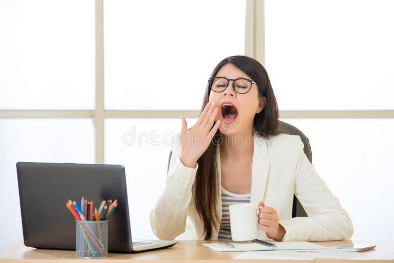 Empresarias asiáticas cansadas que se desvían en el escritorio fotografía de archivo libre de regalías