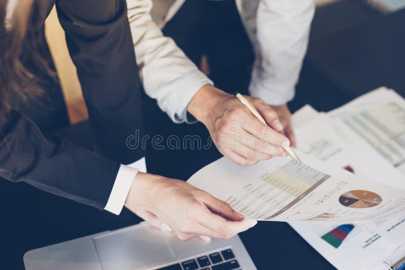 Empresarias asiáticas que llevan a cabo una pluma y documentos del análisis en offi fotos de archivo