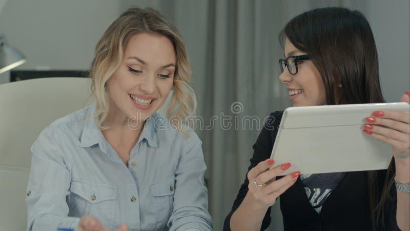 Empresarias con la tableta digital que intercambia ideas en oficina moderna fotografía de archivo libre de regalías