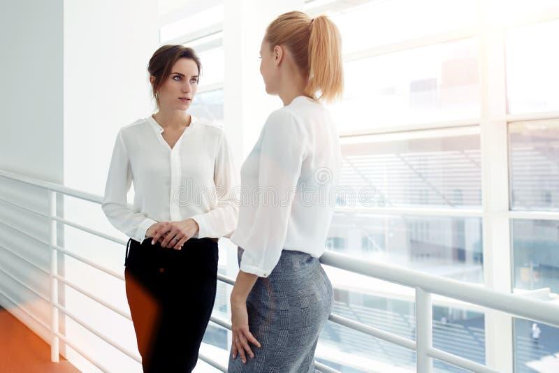 Empresarias confiadas que tienen conversación sobre planes de trabajo mientras que se coloca cerca de ventana grande en vestíbulo imagenes de archivo