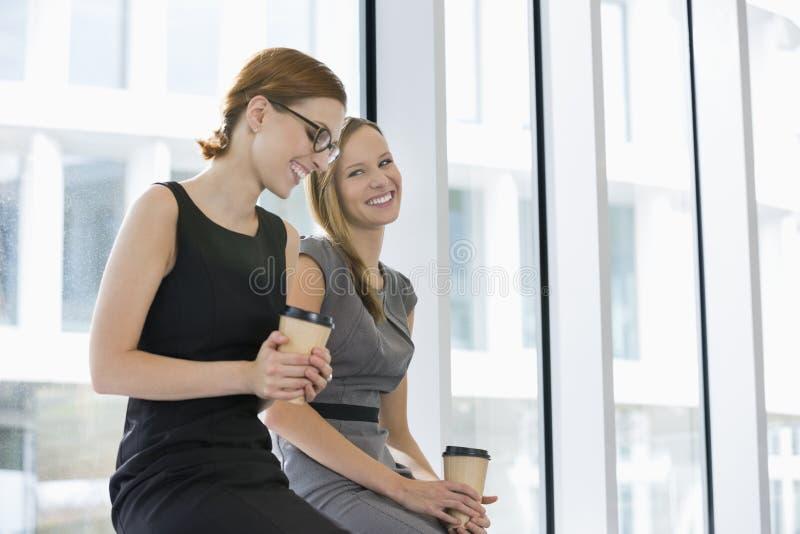 Empresarias felices con las tazas de café disponibles en la oficina fotografía de archivo