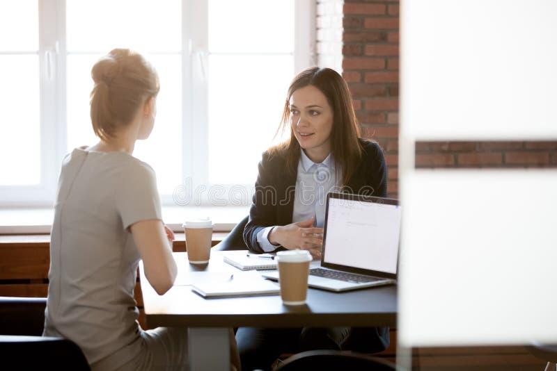 Empresarias jovenes amistosas que hablan la charla en oficina durante c fotos de archivo libres de regalías