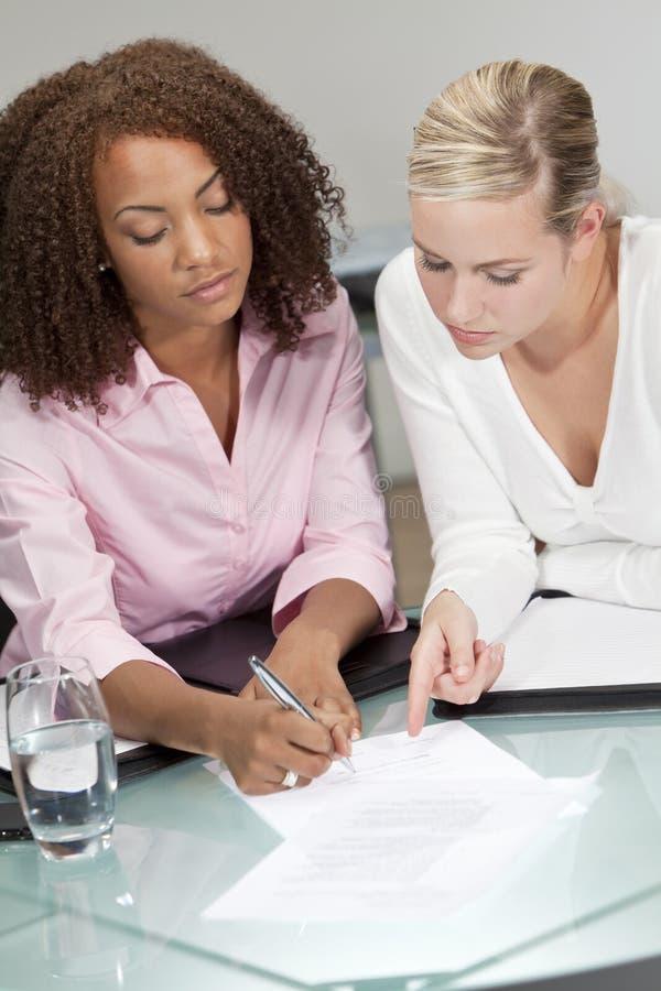 Empresarias jovenes de la raza mezclada que firman un contrato imagenes de archivo