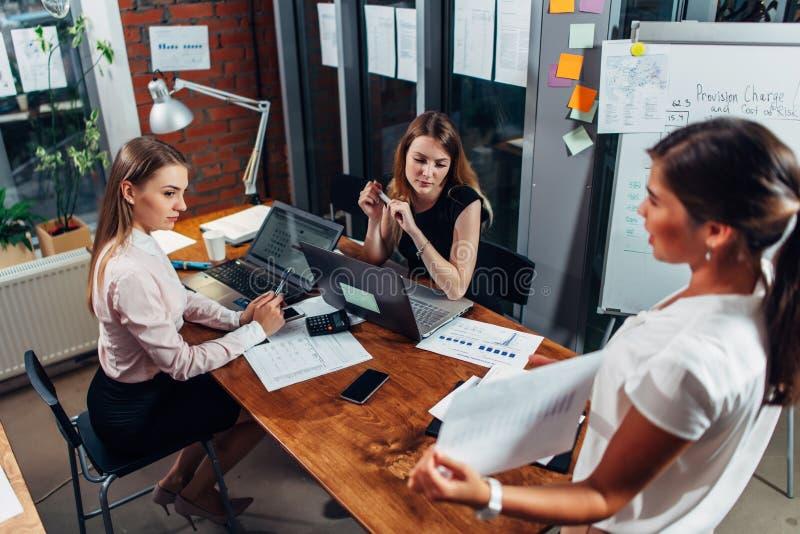 Empresarias jovenes en la presentación Colega femenino que muestra un diagrama que explica nueva estrategia empresarial foto de archivo