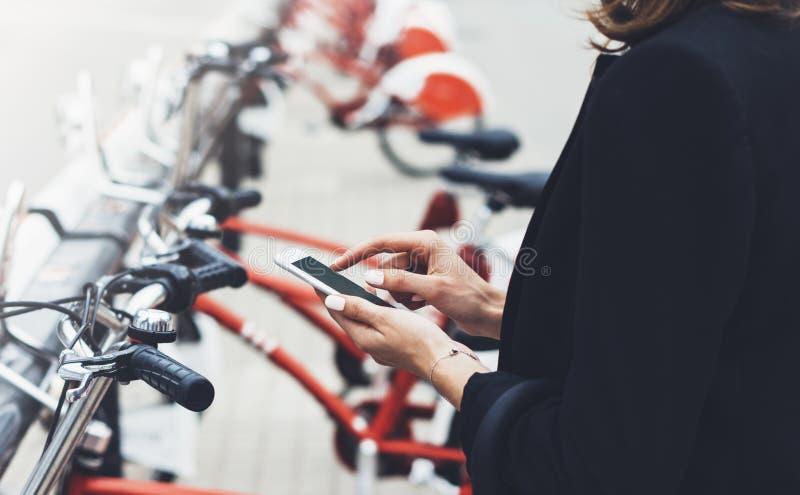 Empresarias jovenes en traje y paraguas negros usando el smartphone, biking y yendo a trabajar en bicicleta de la ciudad en la ca fotografía de archivo