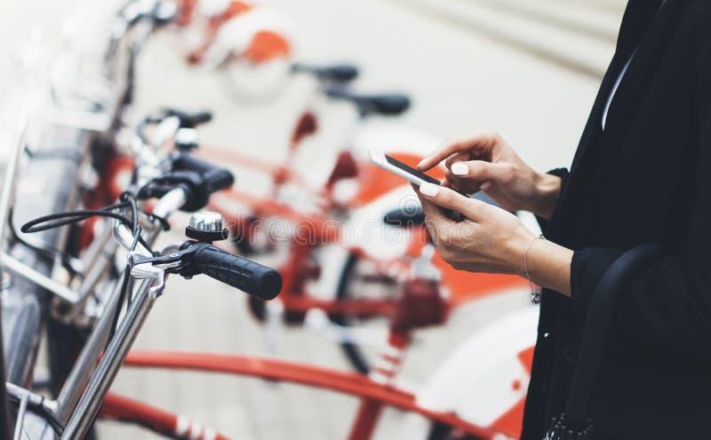 Empresarias jovenes en traje y paraguas negros usando el smartphone, biking y yendo a trabajar en bicicleta de la ciudad en la ca imagen de archivo libre de regalías