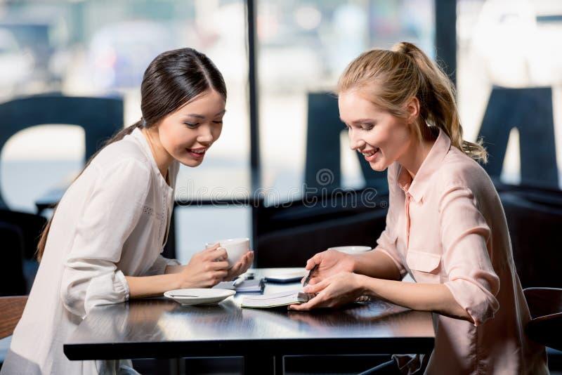 Empresarias jovenes que miran el cuaderno y que discuten proyecto en el descanso para tomar café imagenes de archivo