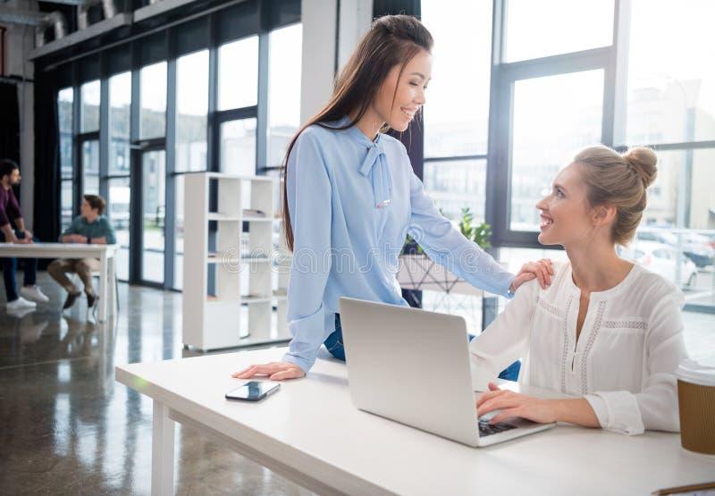 Empresarias jovenes que usan el ordenador portátil y hablando en el lugar de trabajo fotos de archivo