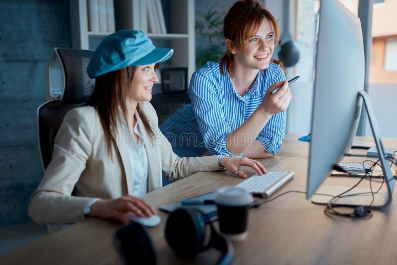 Empresarias que discuten en los oficina-diseñadores que trabajan el overtim fotos de archivo