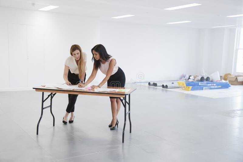 Empresarias que discuten los planes para el diseño interior de la oficina fotografía de archivo