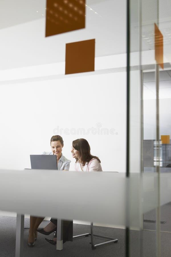 Empresarias que discuten sobre el ordenador portátil en oficina imágenes de archivo libres de regalías