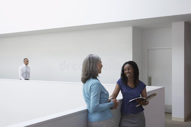 Empresarias que hablan en vestíbulo de la oficina foto de archivo