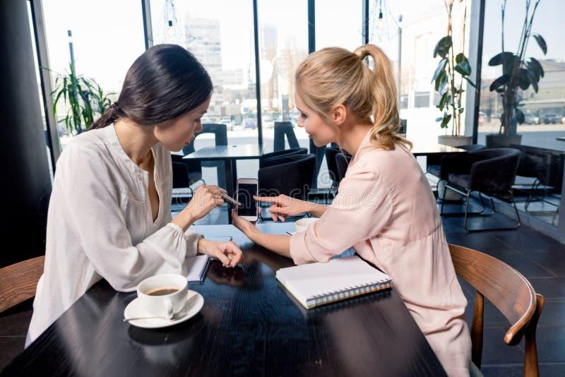 Empresarias que miran smartphone con la pantalla en blanco y que discuten proyecto en el descanso para tomar café fotos de archivo