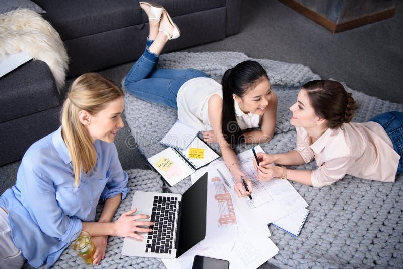 Empresarias que tienen discusión mientras que colega que usa el ordenador portátil fotografía de archivo libre de regalías