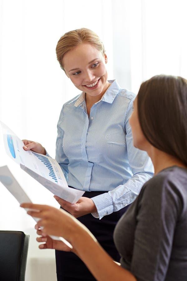 Empresarias sonrientes con los papeles en oficina imagen de archivo