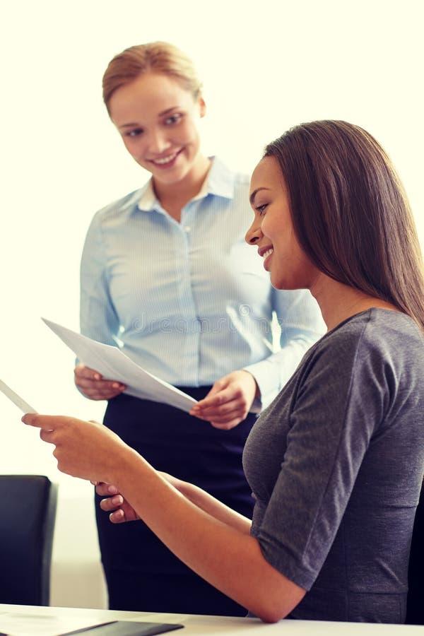 Empresarias sonrientes con los papeles en oficina imagen de archivo libre de regalías
