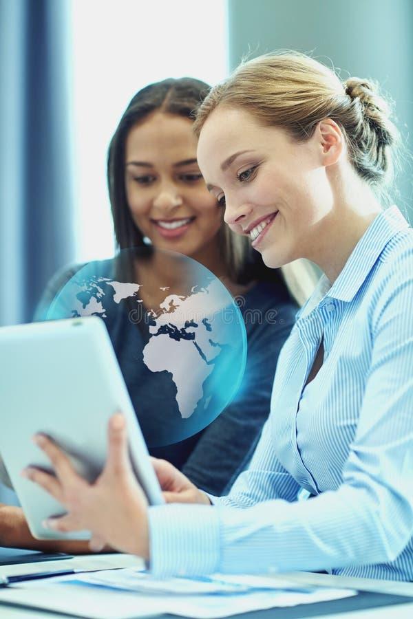 Empresarias sonrientes con PC de la tableta en oficina imagen de archivo libre de regalías