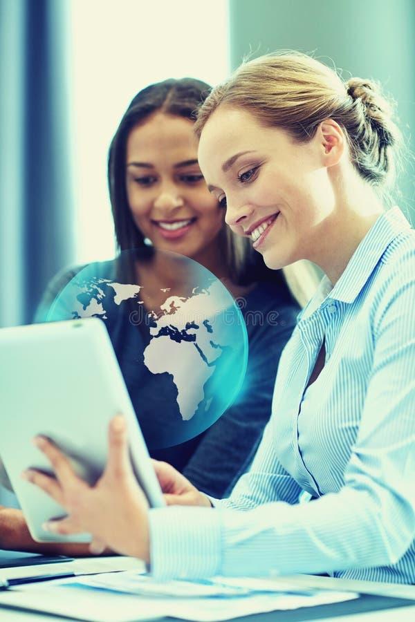 Empresarias sonrientes con PC de la tableta en oficina foto de archivo