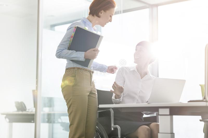 Empresarias sonrientes que discuten sobre el ordenador portátil en el escritorio en oficina moderna imagen de archivo libre de regalías