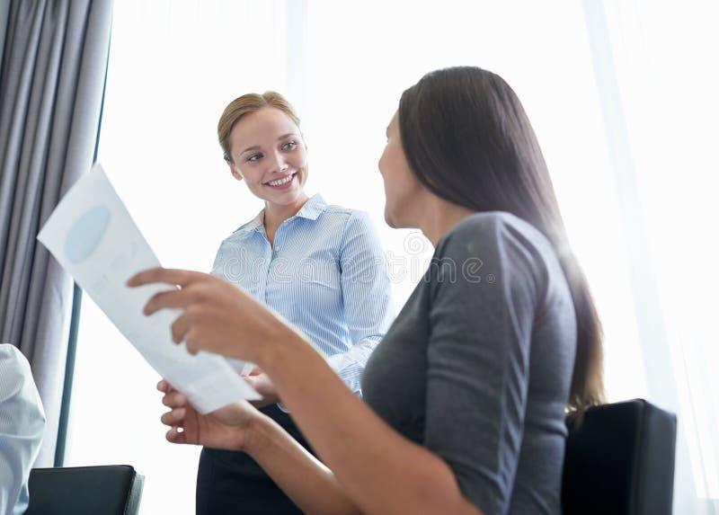 Empresarias sonrientes que se encuentran en oficina imagen de archivo