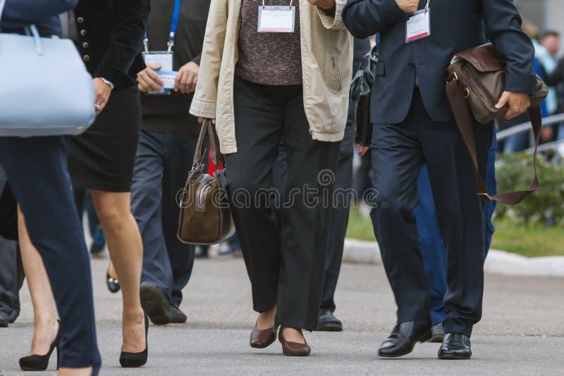 Empresarias y hombres de negocios que caminan a lo largo de la calle en la conferencia o la exposición fotos de archivo
