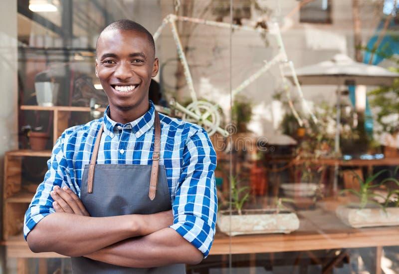 Empresario africano sonriente que se coloca detrás de un contador de su café fotos de archivo