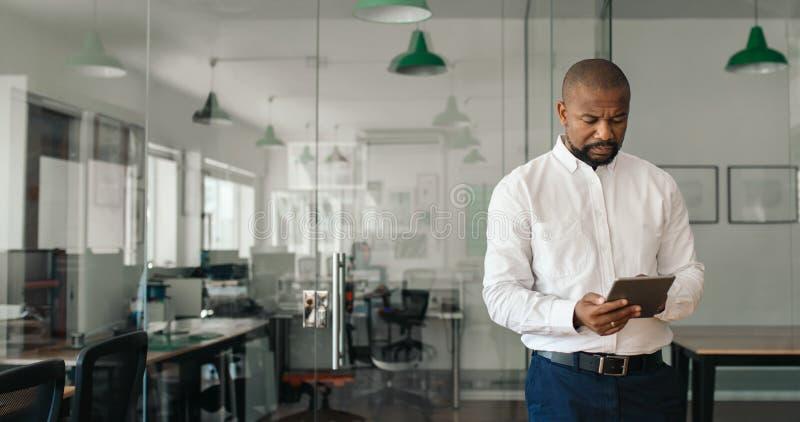 Empresario afroamericano maduro usando una tableta en una oficina fotografía de archivo libre de regalías